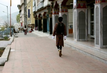 On Thimphu street, a man wearing the traditional 'goh' for men.