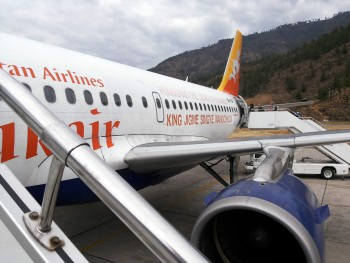 Group members board plane for flight from Paro to Delhi.