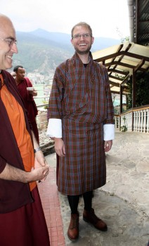 Alex Ryan surprises everyone by arriving dressed in the traditional Bhutanese men's outfit, the <em>gho</em>.