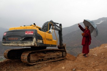 A monk from the Kila Gompa asks the machine operator to allow pilgrimage vechicles to pass.