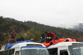 Bhutanese guides and bus drivers pack luggage atop two of the ten buses for the drive to Thimphu.