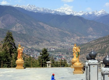 A breath-taking view of the Himalayas rising above the city of Thimphu with several of the offering goddesses in the foreground  as seen from Kunsel Phodrang.